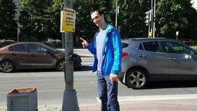 Un jeune homme appuie sur un bouton pour traverser la route S?curit? routi?re L'homme sourit et est heureux banque de vidéos