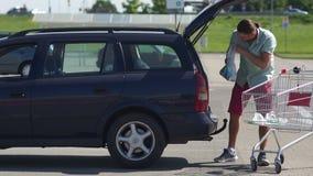 Un jeune homme attirant charge des produits dans le tronc d'une voiture d'un chariot à supermarché Le rôle des hommes dans la fam clips vidéos
