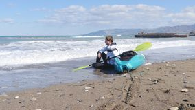 Un jeune homme avec un kayak sur le bord de la mer clips vidéos