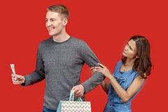 Un jeune homme avec un regard enthousiaste et un sourire heureux sur son visage va au magasin, tenant l'argent et les paniers image libre de droits