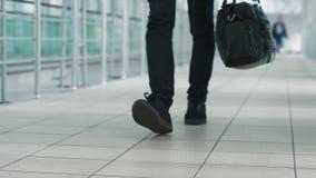 Un jeune homme avec un sac à main marchant dans un terminal d'aéroport moderne clips vidéos