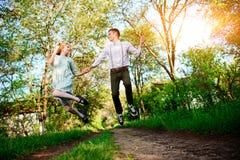 Un jeune homme avec son amie sautent sur la route dans le village ensoleillé Photo libre de droits