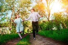 Un jeune homme avec son amie sautent sur la route dans le village ensoleillé Images stock