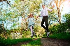 Un jeune homme avec son amie sautent sur la route dans le village ensoleillé Photo stock