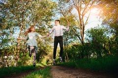 Un jeune homme avec son amie sautent sur la route dans le village ensoleillé Photos libres de droits