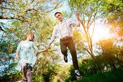 Un jeune homme avec son amie sautent sur la route dans le village ensoleillé Images libres de droits