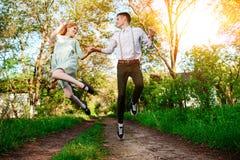 Un jeune homme avec son amie sautent sur la route dans le village ensoleillé Photos stock