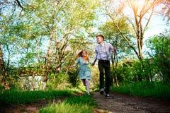Un jeune homme avec son amie sautent sur la route dans le village ensoleillé Photographie stock libre de droits