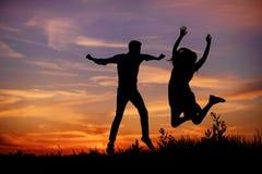 Un jeune homme avec son amie sautent sur la silhouette de coucher du soleil de fond Image stock