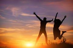 Un jeune homme avec son amie sautent sur la silhouette de coucher du soleil de fond Photos libres de droits