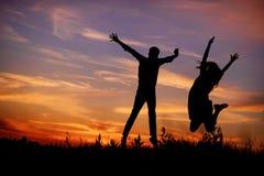 Un jeune homme avec son amie sautent sur la silhouette de coucher du soleil de fond Images stock
