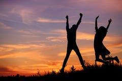Un jeune homme avec son amie sautent sur la silhouette de coucher du soleil de fond Images libres de droits