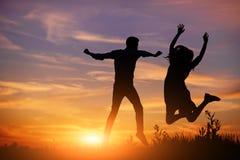 Un jeune homme avec son amie sautent sur la silhouette de coucher du soleil de fond Photos stock