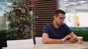 Un jeune homme avec un symbolisme de LGBT passant en revue un téléphone portable dans un café banque de vidéos