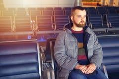 Un jeune homme avec une barbe attend son vol à l'aéroport Photo libre de droits