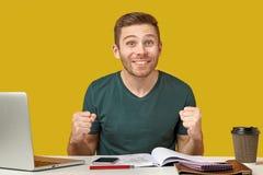 Un jeune homme avec une expression enthousiaste serre ses poings et sourires images libres de droits