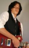 Un jeune homme avec une guitare rouge Image libre de droits