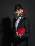 Un jeune homme avec une rose dans des ses dents tenant une boîte de chocolats Images stock