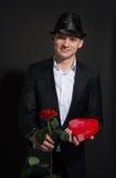 Un jeune homme avec une rose et une boîte de chocolats aiment le coeur du lo Image stock