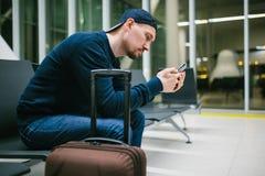 Un jeune homme avec une valise s'assied dans la salle d'attente d'aéroport et utilise un téléphone portable Vol de nuit, transfer Photos stock