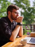 Un jeune homme barbu à l'aide de son ordinateur portable s'assied dans un café photos stock