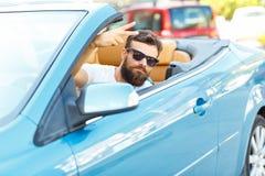 Un jeune homme barbu s'asseyant dans un convertible Photos libres de droits