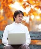 Un jeune homme bel à l'aide de l'ordinateur portable se reposant sur un banc regardant dedans photographie stock libre de droits