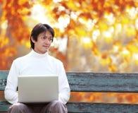 Un jeune homme bel à l'aide de l'ordinateur portable se reposant sur un banc regardant dedans photos libres de droits