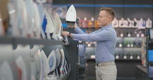 Un jeune homme bel dans une chemise choisit un fer dans un magasin d'électronique grand public c banque de vidéos