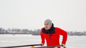 Un jeune homme bel dans une veste et des pantalons noirs de sports en hiver sur une plate-forme ouverte exécute l'otshimaniya des banque de vidéos
