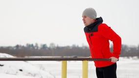 Un jeune homme bel dans une veste et des pantalons noirs de sports en hiver sur une plate-forme ouverte exécute l'otshimaniya des clips vidéos