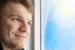 Un jeune homme bel regarde la fenêtre congelée dans le gel et les sourires Bonne humeur en prévision des vacances et photo libre de droits