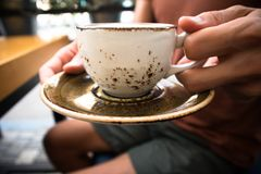 Un jeune homme bel s'assied dans un café avec les amis et le cappuccino chaud potable, détendant, fin d'une tasse Photos libres de droits