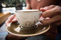 Un jeune homme bel s'assied dans un café avec les amis et le cappuccino chaud potable, détendant, fin d'une tasse photos stock
