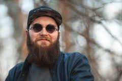 Un jeune homme brutal avec une barbe énorme dans les lunettes de soleil et un chapeau dans les bois au coucher du soleil Photos libres de droits