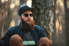 Un jeune homme brutal avec une barbe énorme dans les lunettes de soleil et un chapeau dans les bois au coucher du soleil Photo stock