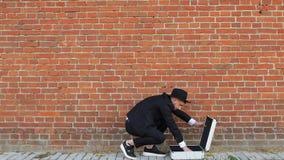 Un jeune homme caucasien dans un costume noir et ouvre une valise en métal avec l'argent avec des dollars sur un fond de mur de b banque de vidéos