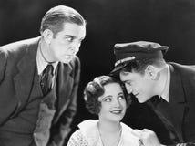 Un jeune homme chuchotant à une jeune femme et un jeune homme différent se tenant près de eux écoutant eux (toutes les personnes  Images stock