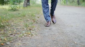 Un jeune homme d'affaires élégant dans les chaussures brunes et le pantalon bleu marche le long du chemin forestier clips vidéos