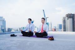 Un jeune homme d'affaires asiatique faisant des sports au dessus de toit photographie stock