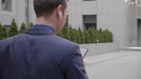 Un jeune homme d'affaires avec les ?couteurs sans fil dans des ses oreilles ?crit un message sur le smartphone banque de vidéos