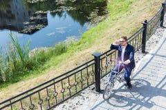 Un jeune homme d'affaires beau roulant sa bicyclette photographie stock libre de droits