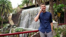 Un jeune homme d'affaires bel s'assied en parc et entretiens sur un smartphone - une rue et des cascades artificielles dans le tr banque de vidéos