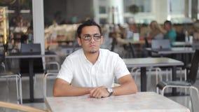 Un jeune homme d'affaires en verres regarde la montre et attend le client clips vidéos