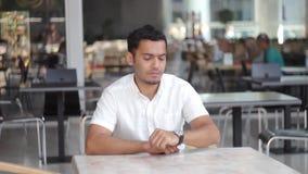 Un jeune homme d'affaires en verres regarde la montre et attend le client banque de vidéos