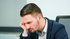 Un jeune homme d'affaires fatigué travaillant des heures supplémentaires image stock