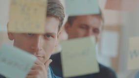 Un jeune homme d'affaires réfléchi regarde le mur avec des autocollants et un mur pour écrire et prévoir fonctionne banque de vidéos