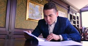 Un jeune homme d'affaires s'assied dans un bureau chic et est dissatisfait avec un contrat de papier, refuse de signer, fâché, dé clips vidéos