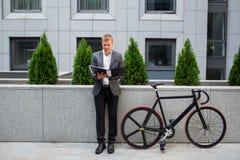 Un jeune homme d'affaires se tenant sur les étapes d'un immeuble de bureaux, avec un dossier des papiers et du vélo Photographie stock