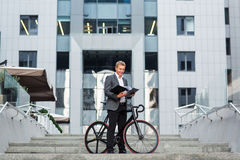 Un jeune homme d'affaires se tenant sur les étapes d'un immeuble de bureaux, avec un dossier des papiers et du vélo Photos libres de droits